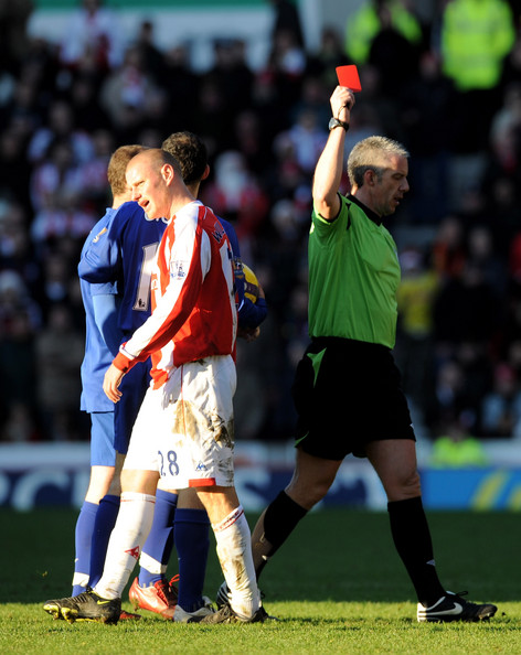 Referee shows the red card to a Stoke City player against Manchester United