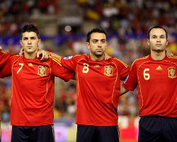 Spain's David Villa, Xavi Hernandez, and Andres Iniesta pictured as they lineup for their country in honor of Spain's national anthem.
